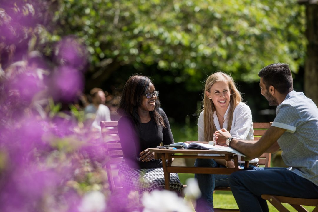 Students chatting at a table in the Broadbent Garden