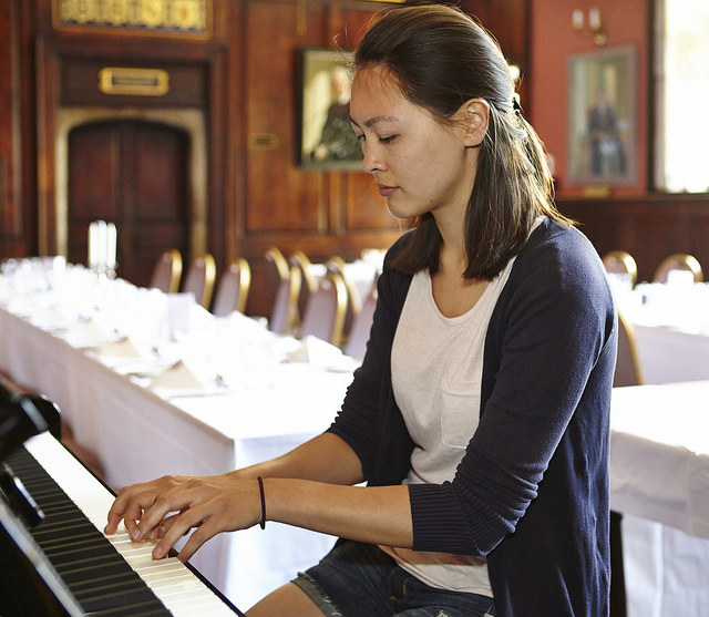 A student playing the piano in the Old Dining Hall