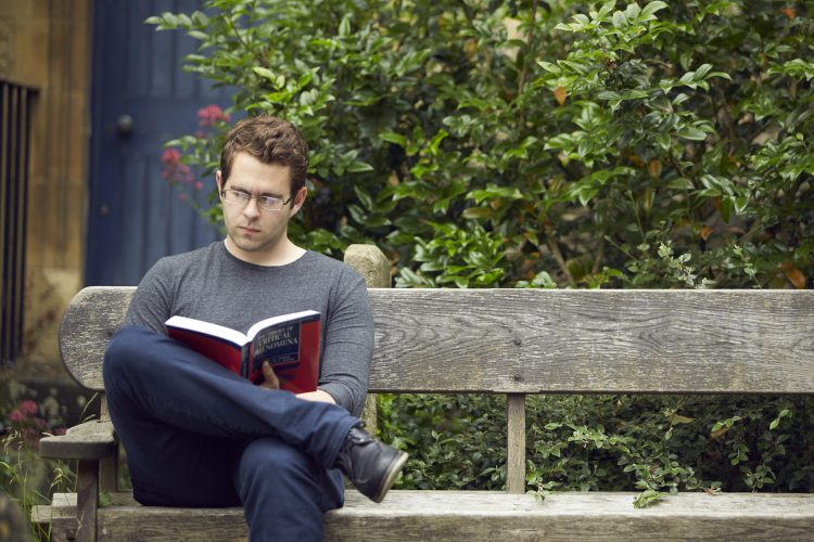 Visiting student Greg reading outside the library in the churchyard