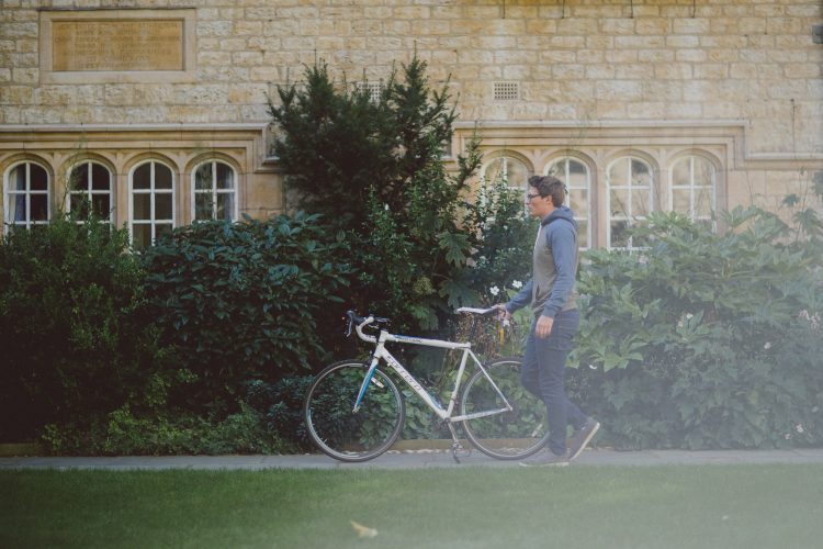Fresher student pushing their bike through the front quad on moving in day