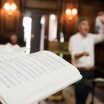 Music book in the Chapel with conductor in background