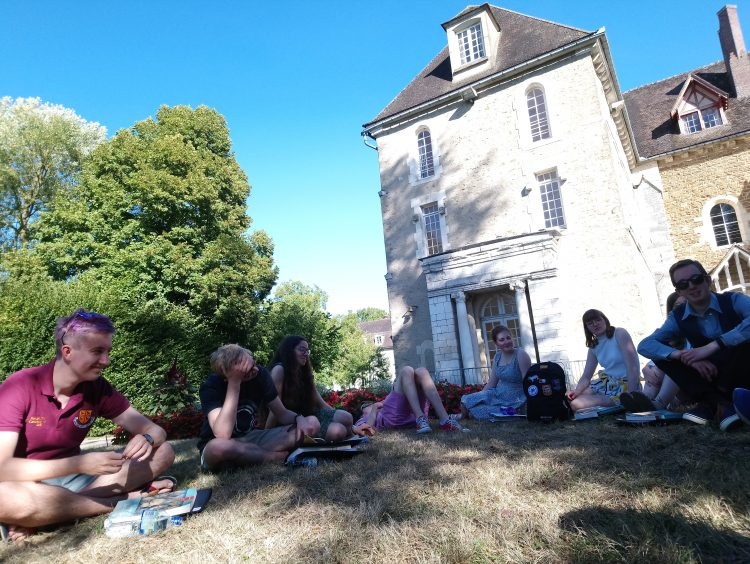 The choir taking some time out to relax in the sunshine during their tour to Pontigny and Paris