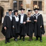 A group of graduates in the Front Quad at Teddy Hall