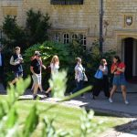 A student leads a tour group through the Front Quad