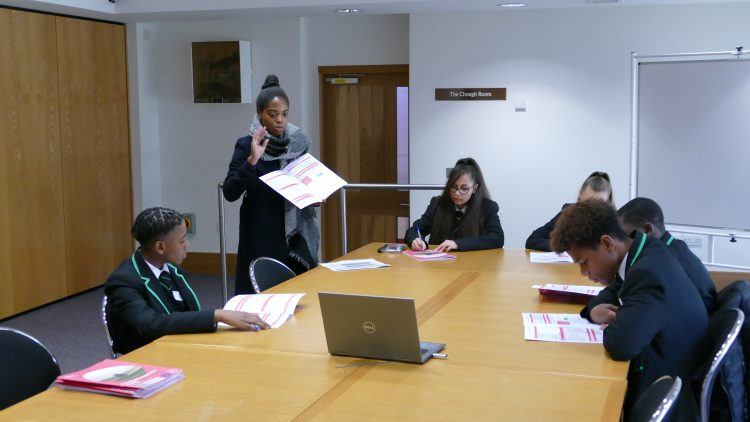 Postgraduate student giving a tutorial lesson to five year 9 pupils, who are seated around a rectangular table, looking at booklets.