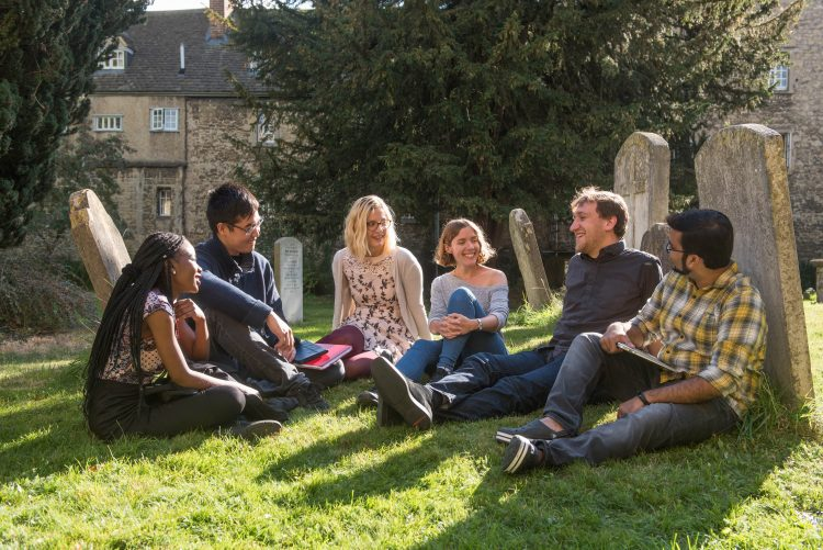 Postgraduate students sitting in the churchyard next to the College Library