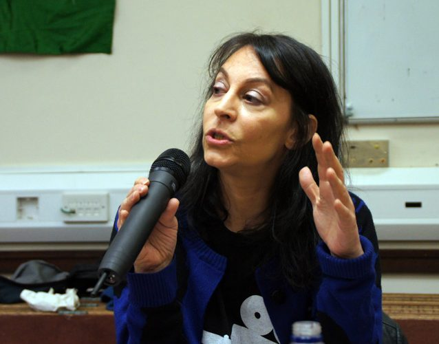 Professor Karma Nabulsi is seated, speaking in to a microphone held in one hand whilst gesturing with the other. She is looking at an unpictured audience and clearly speaking with passion.